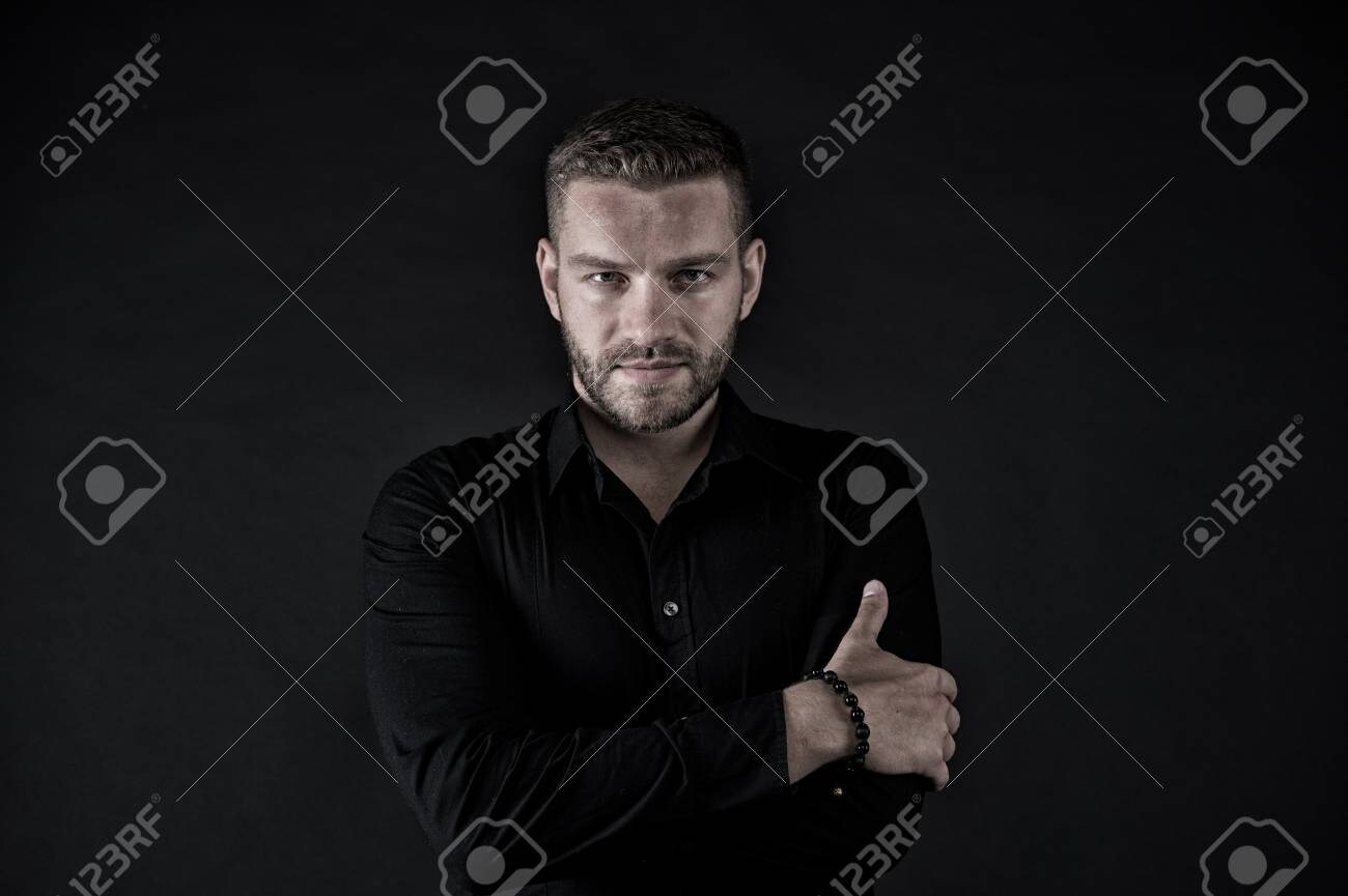 91167093-macho-in-black-shirt-pose-with-folded-hands-man-with-bearded-face-and-stylish-hair-on...jpg